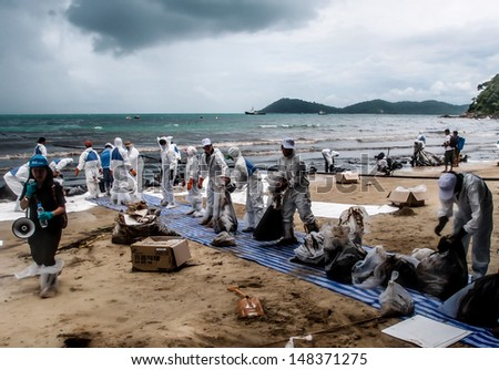 RAYONG -JUL 31: Sand contaminated with oil is transferred from the beach at Rayong, Thailand on Jul 31, 2013. The disaster came from leaked oil from tanker unloading in the sea on July 27.  - stock photo