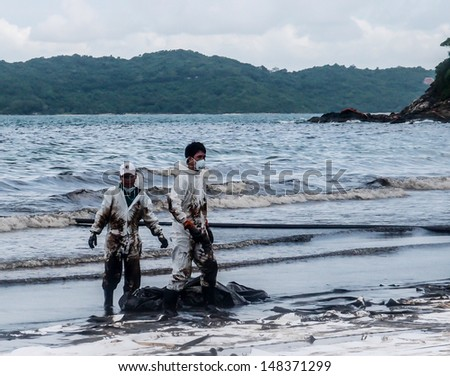RAYONG -JUL 31:Workers in coverall suit correct spilled oil at the beach on Jul 31, 2013 in Rayong, Thailand. Spilled oil came from the accidental leaking during transferring from tanker on July 27. - stock photo