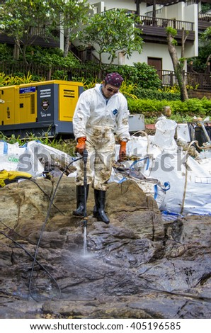 Rayong, Thailand - August 1, 2013: Workers remove crude oil from the Ao Proa beach, Koh Samet Island, Rayong province, Thailand.