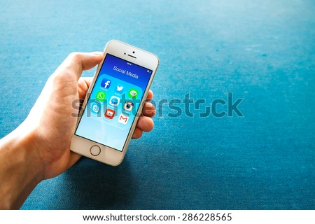 RAYONG, THAILAND - June 03 , 2015: All of popular social media icons on smartphone device screen with hand holding on Apple iPhone 5s. - stock photo