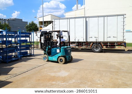 RAYONG, THAILAND -JUNE 10 2015: Forklift lifting cargo from trucks to transport goods to customers in the factory,Thailand - stock photo