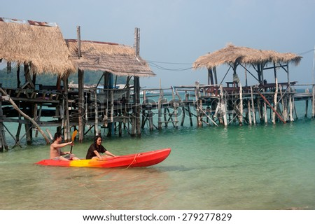 RAYONG,THAILAND-OCTOBER 13 : Tourists paddle canoe relax and happiness in holiday on the sea near traditional wooden bridge at Ao Lungdum on October 13,2013, Rayong Province in Eastern of Thailand. - stock photo