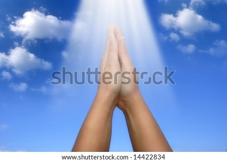 rays of light falling on a female hands in prayer gesture