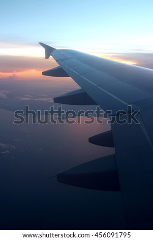 Rays of light in twilight sunset purple orange sky view from window airplane, fly over the ocean at evening time