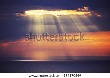 Rays of light shine in water, dramatic sunset - stock photo