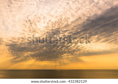 Rays of light shining down from the sky cloud with sea. - stock photo