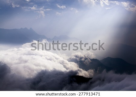 Rays of light shining through clouds - stock photo