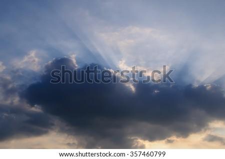 Rays of light shining through clouds, sunset - stock photo