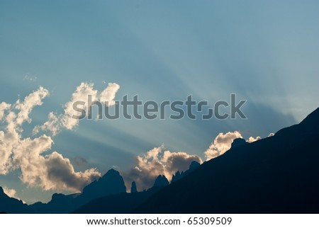 rays of sun peeking out from behind a mountain, creating cuts in the sky at sunset - stock photo