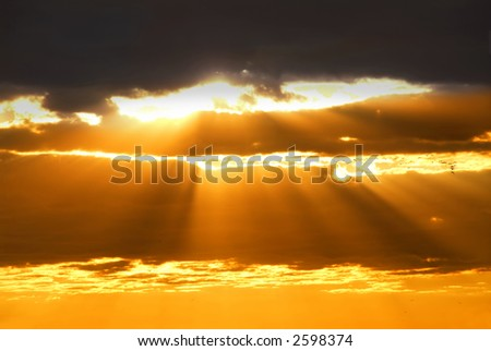 Rays of sun shining through the clouds at sunset - stock photo
