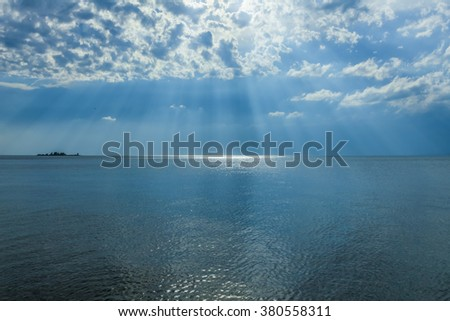 Rays of sun shining through the clouds in blue sky over the sea. - stock photo