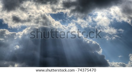 Rays of the sun breaking through storm clouds.  HDR composite (5 exposures) shots. - stock photo