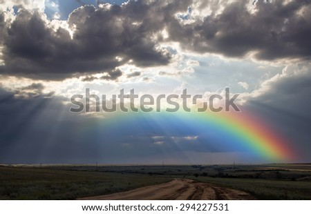 Rays of the sun breaking through the stormy sky, forming a marvelous rainbow - stock photo