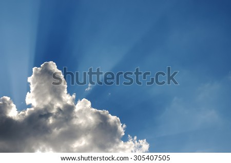 rays of the sun, making their way from behind the clouds against - stock photo