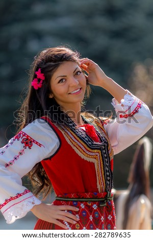 "RAZLOG, BULGARIA - APRIL 13, 2015: A beautiful female Bulgarian folklore dancer posing during the traditional folklore festival ""1000 national costumes"""