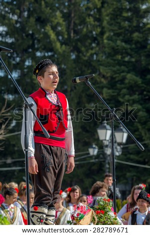"""RAZLOG, BULGARIA - APRIL 13, 2015: A Bulgarian boy singing on the stage during the traditional folklore festival """"1000 national costumes"""" - stock photo"""