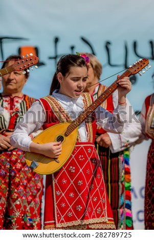"""RAZLOG, BULGARIA - APRIL 13, 2015: A small Bulgarian girl playing on mandolin on the stage during the traditional folklore festival """"1000 national costumes"""" - stock photo"""