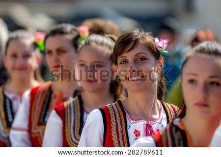 """RAZLOG, BULGARIA - APRIL 13, 2015: A smiling female Bulgarian folklore dancer during the traditional folklore festival """"1000 national costumes"""" - stock photo"""