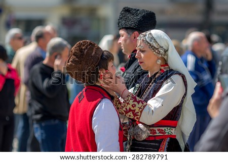 """RAZLOG, BULGARIA - APRIL 13, 2015: Helping with the make-up, during the traditional folklore festival """"1000 national costumes"""" - stock photo"""