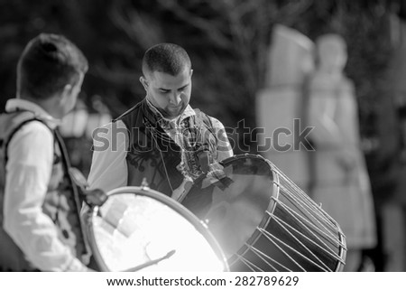 """RAZLOG, BULGARIA - APRIL 13, 2015: Two male Bulgarian folklore drummers performing a show during the traditional folklore festival """"1000 national costumes"""" - stock photo"""