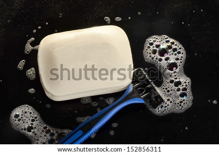 Razor and soap on a black surface/Morning Hygiene/Soap bubble surround soap bar and a razor - stock photo