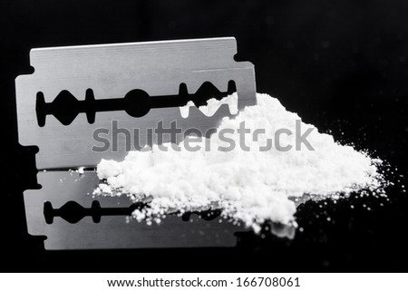 Razor Blade closeup on drug powder on black background with reflection - stock photo