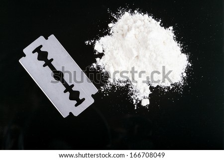 Razor Blade closeup with white  drug powder on black background with reflection - stock photo