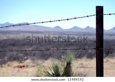 Razor-wire border fence in Arizona to prevent cattle but not people from crossing the border - stock photo