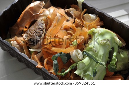 Re-used plastic container of vegetable food waste from the kitchen for home recycling by composting. - stock photo