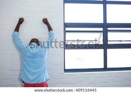 Rea view of upset man leaning against wall in office - stock photo
