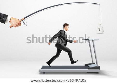Reach a goal concept with businessman running on a treadmill for money  - stock photo
