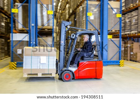 Reach truck forklift driving past an isle in a warehouse at speed. A panned image, with stock and cardboard boxes in the shelves of the storage racks. Conceptual image about internal logistics - stock photo