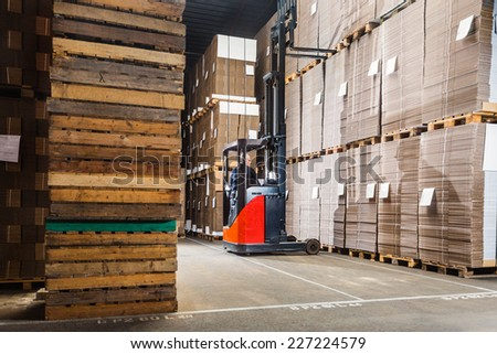 Reach truck forklift lifting a pallet from the top shelf in a large warehouse - stock photo