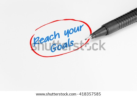 Reach your goals text written on white paper - Business Concept