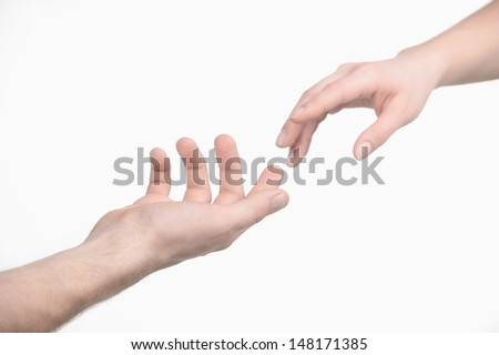 Reaching a hand. Close-up of human hands trying to reach each other - stock photo