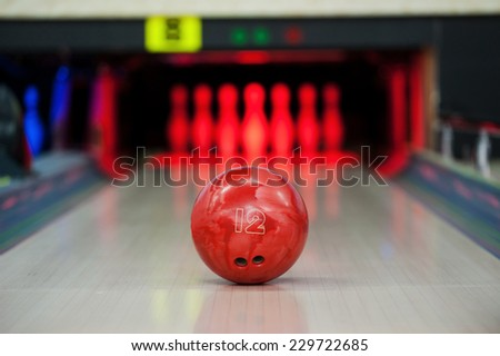 Reaching the goal. Close-up of bright red bowling ball rolling along bowling alley   - stock photo