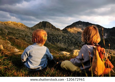 Reaching the top, two children watching the mountain peak - stock photo