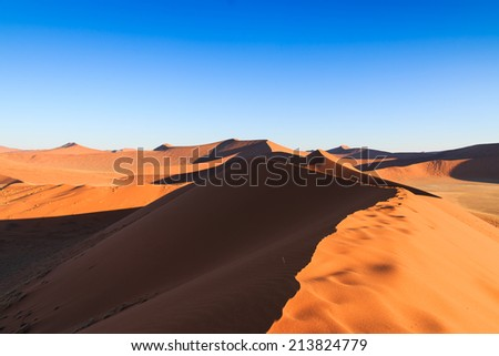 Reaching top red dune of always shifting sand. Sossusvlei, Namibia, Africa. - stock photo