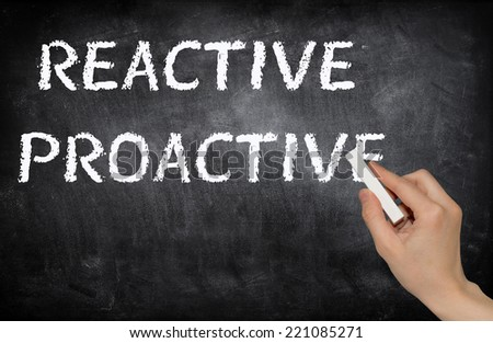 Reactive and proactive written on a blackboard with white chalk - stock photo