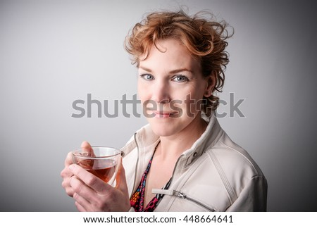 Read haired middle aged woman drinking tea. Relaxation concept. Stress free female model looking into camera. - stock photo