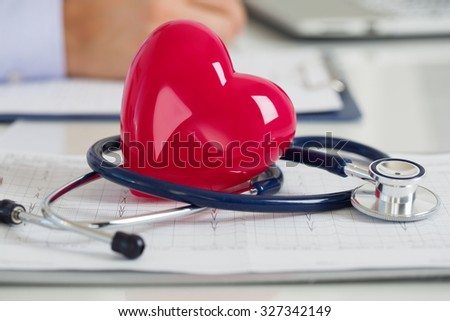 Read heart and stethoscope laying on cardiogram chart at doctor's working table closeup. Medical help, prophylaxis, disease prevention or insurance concept.  - stock photo