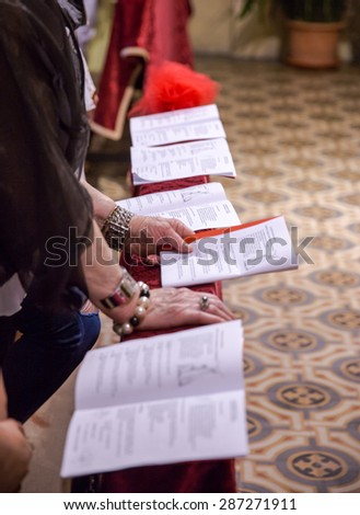 read the booklet during  a religious service - stock photo