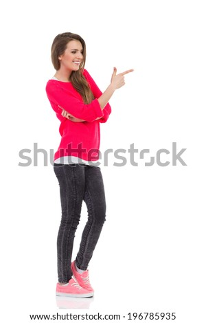 Read this. Smiling young woman pointing at empty space. Full length studio shot isolated on white. - stock photo