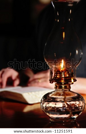 Reading a Bible by vintage oil lamplight - (shallow focus point on antique oil lamp). - stock photo