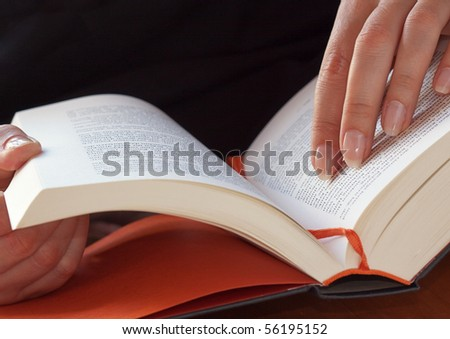 Reading a book. Hardcover book on a library desk. - stock photo