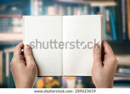 Reading a book in the library. First-person view - stock photo