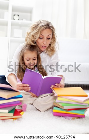 Reading a book with mom - little girl first spelling exercises