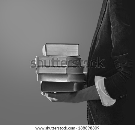 Reading and student college concept. Man holding a pile of old books for studying.  - stock photo