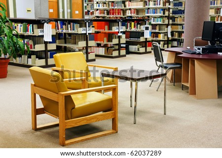 Reading area and computers at a university/college school library. Colorful yellow leather chairs. - stock photo