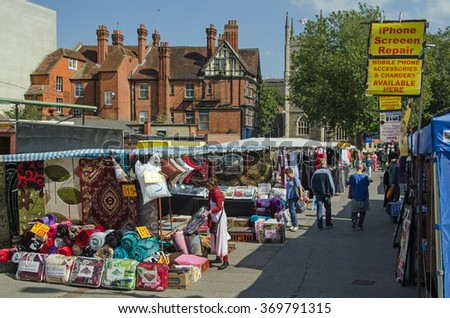 READING, BERKSHIRE - SEPTEMBER 10, 2015:  A sunny afternoon at the market on Hosier Street in Reading, Berkshire.  Shoppers browsing various goods including soft furnishings, electronics and clothes. - stock photo